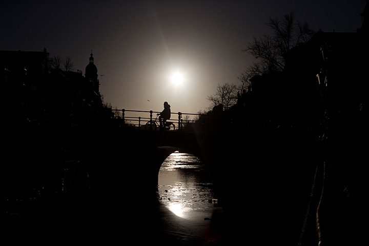 inothernews:  A cyclist is silhouetted while crossing the Keizersgracht in Amsterdam, the Netherlands.  (Photo: Peter Dejong / AP via The Guardian)