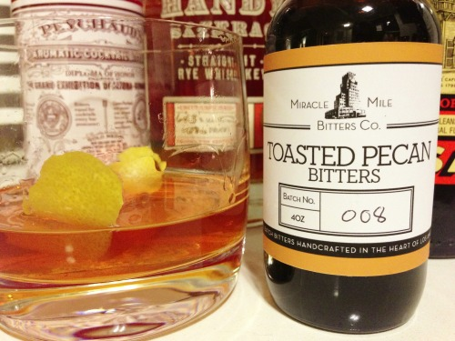 To paraphrase Hunter Thompson, once you get locked into a serious bitters collection, the tendency is to push it as far as you can. Like most cocktail nerds, I have a shelf full of exotic bitters I rarely use, or only use for a particular drink once in a blue moon. Occasionally, though, I discover a true gem I want to find an excuse to work into every drink I make. My friends Courtney & Robert just sent me a bottle of Toasted Pecan bitters from Miracle Mile Bitters Company in Los Angeles, and I'm already convinced I'll be using them regularly.  While its essential sweetness would seem to make bourbon the obvious Southern-inflected pairing for pecan bitters, the first spirit I was eager to test drive my new acquisition with was rye. Inspired by the rye pecan pie Brooklyn's Marlow & Sons makes during the holidays, I had a feeling the spiciness of rye might be a perfect counterpoint to the sweet nuttiness of the bitters, and I was right. They were lovely in a Rye Old Fashioned, if perhaps a just a touch sweet for my taste (a problem adding additional aromatic bitters solved), but I was really impressed with how nicely they rounded out a Sazerac. A couple drops along with the usual Peychaud's Bitters adds a nice extra layer of depth and helps soften the edges of a normally rather stiff drink.
