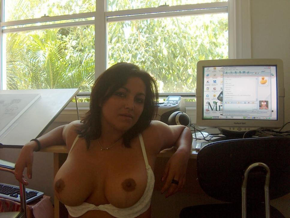 Woman bares breasts in front of her computer …