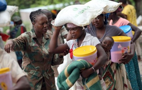 A South African National Defence Force soldier helps hand out food and goods to people displaced by floods at Licilo, Mozambique, yesterday. However, the relief supplies are often not adequate for the needs Picture: KEVIN SUTHERLAND