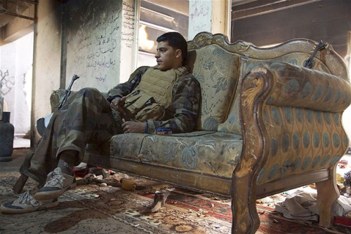 chris9076:  A Free Syrian Army fighter sits on a sofa inside a house in Deir al-Zor, Syria.