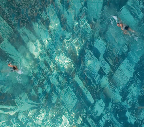 view-from-up-here:  NY under water. The eye-catching swimming pool in Mumbai, India, has been built to raise awareness about the threat of sea level rises as a result of global warming.   It was constructed by attaching a giant aerial photograph of the New York City skyline to the floor of the pool.
