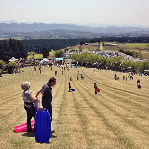 Mom and Dad prepare to sled down a grassy hill. Awesome times in Japan.