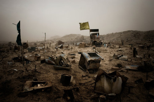 Ten Years in Iraq - SADR CITY, BAGHDAD - MARCH 2008: Pieces of scrap metal and boxes mark graves in a makeshift cemetery for victims of sectarian killing, on the eastern outskirts the poor Shia slums of Sadr City. The bodies, shot by Shia militiamen, are collected from a nearby killing ground called al-Sadda, and buried by locals. (Photo by Ghaith Abdul-Ahad/ Reportage by Getty Images). See more iconic images from the Iraq War here.