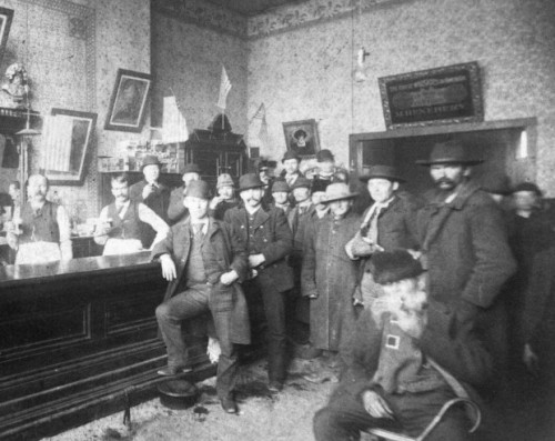 Interior of a bar in the First Ward's infamous Levee District, 1899, Chicago. UPDATE: From Mel Theobald:   Levee Saloon photo The Feb. 8 photo of the Levee Saloon is in the McLean County Museum of History archive as a saloon in Bloomington, IL bearing an inscription with the name of one of the men. You might want to check this out by contacting the historian there. Can you verifiy the source you have for it? From Calumet 412: The original source, a beer culture flikr page, no longer exists. I will contact the historian. Thanks for the tip!