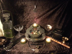 elja-dreaming:  My current altar setup. Far left: Element of Water. Bottle of moon water, chalice, offering bowl. Near left: Element of Fire. Athame and consecrated dual use lighter (it has both a regular and jet flame capability. I find the jet flame fantastic for lighting incense coal) Far right: Element of Earth. Crystals and jewelry. Near right: Element of Air. Incense burner and the small spoon I use for picking up powdered incense; and wooden recorder. Center: Element of Spirit. Pentacle circlet, crystal ball, consecrated fountain pen, fountain, altar pentacle hanging above fountain and Owl pin that was a gift from my partner as a symbol of Blodeuwedd. And the finishing touch, the three green tea light holders that can be used for the Triple Goddess or other use of three. NOTES ON THE USE OF THE FOUNTAIN: I chose the fountain because it contains, and thus, represents, the four main elements. Water is quite obvious (its a fountain). Earth is the stones that litter the top and middle divisions. Fire is in the candle that burns atop it, and Air is in the scent that comes from the scented candles that I have a tendency to use in there.