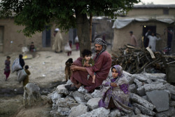 fotojournalismus:  Pakistani daily labourer, Wakeel Mohammed, 38, sits on a roadside with his daughter Halimah, 1, on his lap and his relative Khadijah, 7, right, near their home, in a poor neighbourhood on the outskirts of Islamabad, Pakistan on April 11, 2013. [Credit : Muhammed Muheisen/AP]