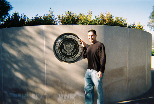 Ooh, look at me!  Here I am standing next to the Presidential Seal at the rear of Ronald Reagan's tomb on the grounds of the Reagan Library in Simi Valley, California in December 2004.  For some reason, I look 20 years younger in this photo than I do now even though it was only nine years ago.  I blame Tumblr for the rapid aging and my noticeable physical deterioration.  Also, ice cream. If you're wondering why I look so happy to be standing next to somebody's grave, it's not because I'm a ghoul.  I was just stoked because this was my first-ever visit to a Presidential Library.  I went to Nixon's in Yorba Linda the next day.  I revisited the Reagan Library in 2010 before I moved out of California and, of course, I spent so many hours at the LBJ Library during my year living in Austin that I think people began to wonder if I was an exhibit.