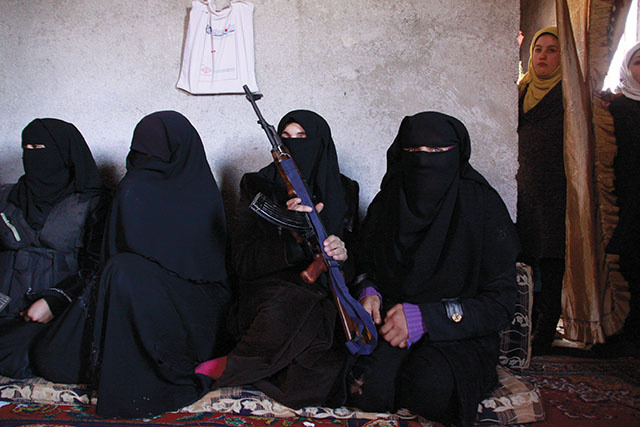 Meet the Ladies of the Free Syrian Army – They Have Guns, Dead Families, and Nothing to Lose An all-female FSA brigade gathers inside Auntie Mahmoud's house in Atmeh, Syria. Photos by Andreas Stahl. Just a few hundred meters from the Turkey-Syria border lies Atmeh, a once quiet farm town that, in recent months, has become a safe haven for the Free Syrian Army. Fifteen thousand Syrians roam freely, displaced by the civil war, along with various brigades and Islamic militants. There's also Auntie Mahmoud's house—a meeting place for a local all-female unit of FSA fighters. Auntie Mahmoud is a tough old broad who's happy to shake your hand, even while other Syrian women in town naturally shy away. She lives in a small house across the street from a FSA base and makes it her business to know everything that goes on around her. Her living room is carpeted with thin mattresses, and when we visited her recently, we found eight women, draped in black hijabs and seated with Kalashnikovs resting on their laps. These brave women are members of the FSA who are ready to plunge into intense urban firefights alongside their male counterparts, if needed. Though they originally hail from cities like Aleppo, Hama, and Idlib, many of them now live in the camp near Atmeh and share strikingly similar backgrounds: each of their husbands was killed or imprisoned while fighting Assad's regime, their homes were leveled by shelling and other attacks, and over the course of two years of Syria's civil war, they all grew tired of sitting on the sidelines and waiting for a favorable outcome to the conflict.  Am Ar'ou, a 37-year-old former law student from Aleppo, is the leader of the brigade. Wearing a military vest and with her face completely veiled in niqab, she stroked her rifle as she recounted how her husband was arrested only because he had a beard and prayed five times a day. She worked closely with the FSA when the war began, storing weapons and supplies in her home until the cache was discovered, shelled, and destroyed. After the attack, she spent three months in the hospital with jaw, hand, and back injuries. Once discharged, she had no home to return to and became a refugee in her own country. She traveled to the camp in Atmeh and soon found other women who also had nothing but one another, sad stories, and some guns. Safa, who has been involved with the revolution against Assad from the beginning, walks through the streets of Atmeh. The women in Am's brigade have declared jihad against President Assad in the name of freedom, democracy, and women's rights in an overwhelmingly male-dominated society. But they're also wary of some of their allies because Atmeh is a hotbed of rebel activity and home to hard-line Salafist Islamic groups such as Jabhat al-Nusra (one of the best-known Islamic groups fighting in Syria today, who were recently added to the US's list of terrorist organizations), the al-Farouq Brigade, al Qaeda, and various other foreign mujahideen fighters. This has made Am and her comrades' mission particularly difficult to execute. Jabhat al-Nusra, for example, support the women in theory but refuse to fight alongside them or allow them to carry their weapons openly. Even though they're all opposed to Assad, the Islamic rebel groups are determined to create an Islamic state in Syria, while most Syrians are opposed to this idea. Am and her brigade are devout Muslims, too, but they don't want an Islamic state; they want a democracy. Continue