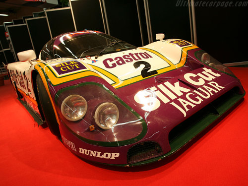 Jaguar XJR-9 LMCountry of origin:Great BritainProduced in:1988Numbers built:6 + 2 earlier chassisDesigned by:Tony Southgate for TWRPredecessor:Jaguar XJR-8Successor:Jaguar XJR-12With five victories in seven years Jaguar&#8217s reigned supreme at Le Mans in the 1950s, but rule changes left the highly successful D-Type obsolete after the 1957 season. Although the Works team would not field a racing car for many years, the racing department did develop the Lightweight competition version of the E-Type and the V12 engined XJ 13. After a heavy accident the XJ 13 project was halted, but the V12 engine was further developed and used in Jaguar&#8217s road cars. In the 1970s racing was left to privateers, although some did receive factory support through the proverbial backdoor.  In the early 1980s two of the most successful Jaguar privateers made plans to bring the marque back to Le Mans. Both Bob Tullius&#8217 US based Group 44 and Tom Walkinshaw&#8217s Britain based TWR had vast experience with the latest version of Jaguar&#8217s V12 and felt it could be a strong competitor in the newly created Group C class. This would mean taking on the mighty Porsches and that seemed virtually impossible without some structural factory support. Surprisingly this was granted to both teams with Group 44 continuing to focus on the American IMSA GTP Championship and TWR on the Group C World Championship. This strategy would give Jaguar two chances at Le Mans glory.  Group 44 had a clear head start as their mid-engined Jaguar XJR-5 was ready late in 1982. The car sported an aluminium monocoque and used the Jaguar V12 engine as a fully stressed member. The car was raced with considerable success in 1983, highlighted with a class win at Road Atlanta. With an eye at Le Mans, a computerized Fuel Injection system was developed over the winter to replace the Weber Carburettors previously used. The XJR-5 raced at Le Mans with factory backing in 1984 and 1985, with a class victory in the second yea