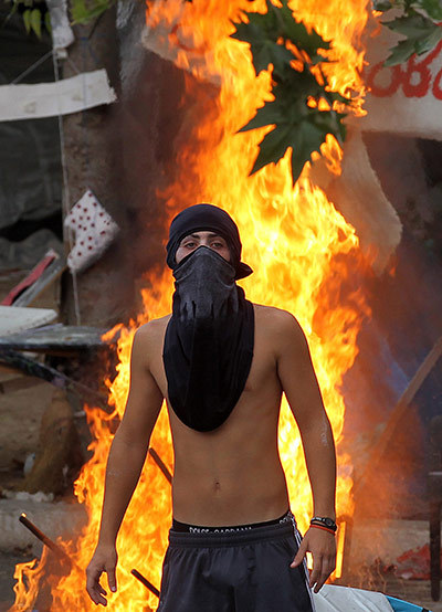 Shirtless Greek protestor framed by flames. HOT!