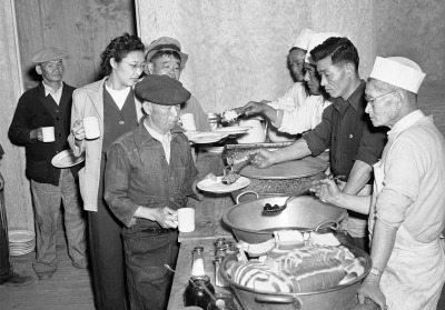 """Japanese Americans removed from their Los Angeles homes line up at Manzanar Relocation Center, in California, on March 23, 1942, for their first meal after arrival at the camp. Rice, Beans, Prunes, and bread were included in the menu."" (AP)"
