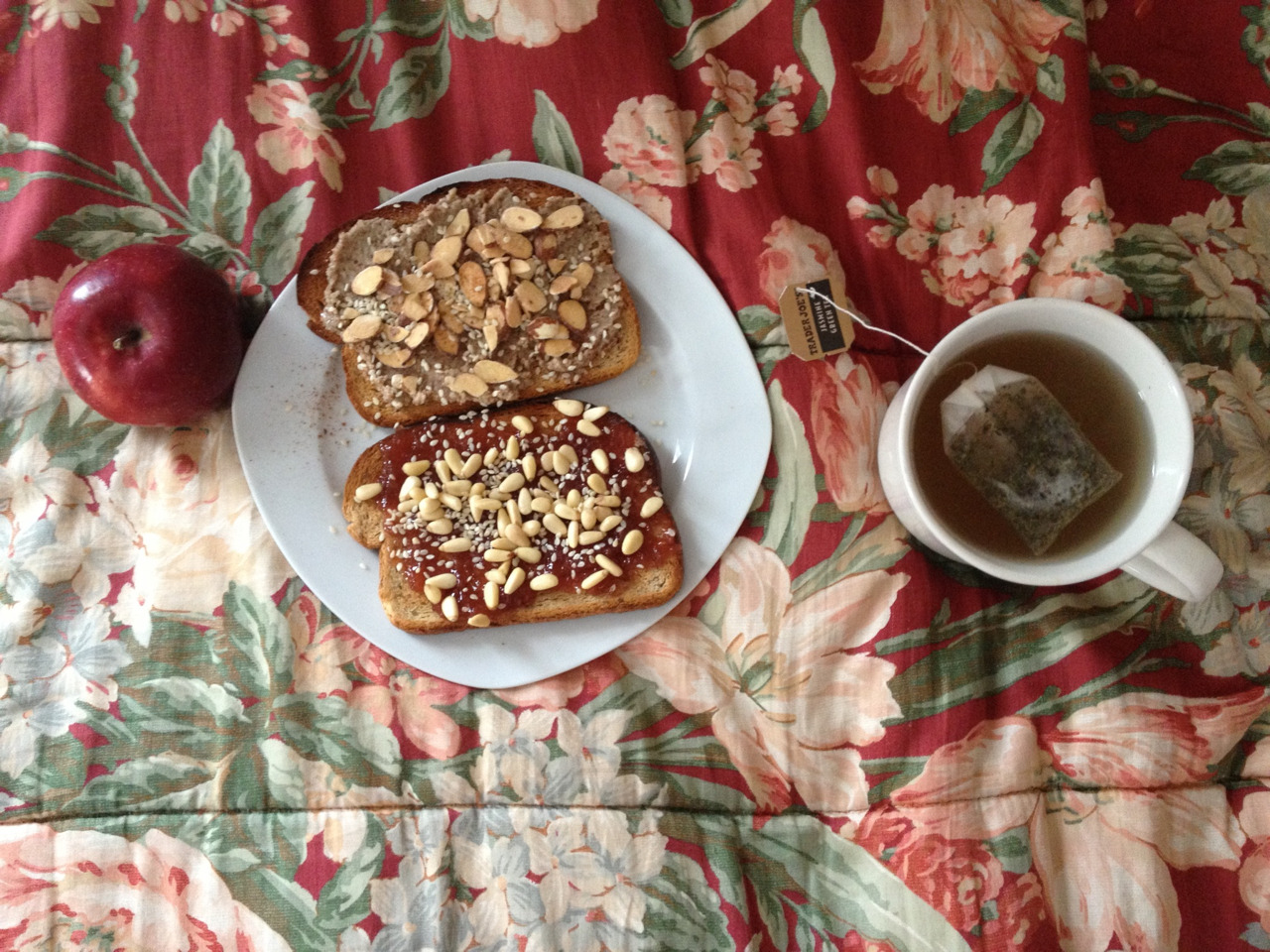 Oh my breakfast okay lets see so we have: rye toast with pecan butter cinnamon slivered honey roasted almonds and sesame seeds on one slice then raspberry peach champagne jam with pine nuts and sesame seeds on the other, an empire apple, and jasmine green tea with orange blossom water and honey way to start the day~