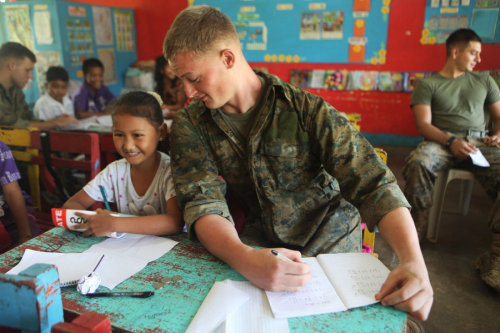 Marine pretending to cheat off a 4th graders math exam. - Phillippines