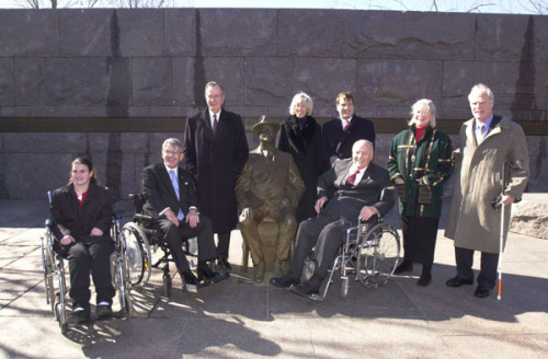 George H.W. Bush visits the life-size sculpture of Franklin D. Roosevelt seated in a wheelchair at the FDR Memorial in Washington, D.C. The FDR Memorial was first dedicated on May 2, 1997.  Landscape architect Lawrence Halprin had designed the memorial with special attention to accessibility, however, the original design did not include a statue of FDR in a wheelchair.  The 32nd President had used one after his legs were paralyzed from polio in 1921.   Advocates for the disabled protested that there should be an accurate depiction of FDR.  A statue of FDR in a wheelchair would, they argued, increase awareness of disability history and of the accomplishments of people with disabilities.   President Clinton agreed, and sent legislation to Congress to modify the memorial with a sculpture of FDR in his wheelchair.  The statue was unveiled in January 2001, and now greets visitors at the entrance to the FDR Memorial.   Photo: George H.W. Bush, Secretary of the Interior Gale Norton, advocates for the disabled Michael Deland and Alan Reich, and other dignitaries visit the Franklin D. Roosevelt Memorial.  2/12/03.    More - Disability History from the National Archives