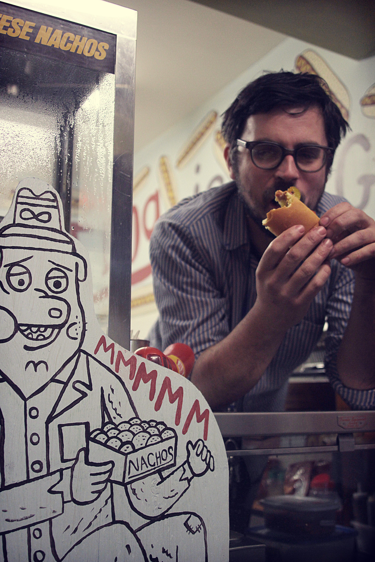 "The Hot 'n Dog: Where Franks & Comics Collide Shorty after 3pm each weekday, kids from two Toronto grade schools hang out at a tiny neighborhood hot-dog joint. This is the Hot 'n Dog, where the specialty is toppings. Lots and lots of toppings. Behind the counter is Keith Jones, a cartoonist (and hot dog connoisseur) responsible for graphic novels like dystopian pet epic Catland Empire and abstract-ish activity book Colour Me Busy. Jones loves comics, frumpy cartoon animals and filling up spaces — interests that synced with a Toronto entrepreneur who, a year ago, decided to open a hot dog shop. Now co-owner, Jones is dressing $2 hot dogs with comic artistry, along with toppings (100 of them in all) that range from wasabi to flaxseed to rainbow sprinkles. We asked Jones about renovations, post-apocalyptic BBQ cars and, of course, hot dogs. This is kind of an odd place for a comic artist to end up. Do you have any particular feelings toward hot dogs? I think hot dogs are hilarious. As a kid, they were one of my favorite foods. I like that you can decorate them, just put junk on them. A hundred different things. I made a great dessert dog just the other day. It had two different kinds of jam, chocolate chips, marshmallows, pretzels and bacon bits, maple syrup. Then I mixed in Hickory Sticks and graham crackers. It looked insane. Also I made a chili cheese dog with 10 different things on it for fun. Supposedly, there are kids who have come in here and gotten all 100 toppings on their hot dogs. I haven't done that yet. [[MORE]] How did you come to run the Hot 'n Dog? I met George Karpouzis when he opened up a comic book shop in Kensington. I hung out at that comic book shop all the time. He was trying to sell the Hot 'n Dog to somebody else, but that didn't work out. I woke up one day thinking, ""I should own that."" So I just went and asked him. I wanted this place to look like a cartoon-land. He knew what I wanted to do with it, and that made him excited to have me. Is it true you enjoy filling spaces like this? Oh yeah. I don't know why, it's obsessive to me. Might be an insecurity, I don't know, but it's fun! I've done a couple spaces like this before, redecorated a bar and had some gallery shows. Usually I come in and I don't know what I'm doing, start with a couple things and new ideas flourish. I remember when I came up with ""My Hot Dog is Bigger Than Yours."" I was just staring at this white empty space wondering how the hell I'm going to fill that in. I came up with that line and just laughed for about a half-hour. Great ideas lead to more ideas. I want to make those rotor fan blades up on the ceiling hot dogs. That's an idea I just came up with. And you're selling comics here too? Yeah, I just brought in a couple comics that I made, to sell. I'm actually going to make a newspaper called Hot Dog Times. It'll have different cartoonists from all over doing hot dog-themed things. Articles all about hot dogs. I've talked to five or six artists who want to do stuff. What do you like about drawing rude animals? I don't know, it just happens that way. I just think they're weird. I like cartoon characters, but I want them to be doing things that cartoon characters don't usually do, like swearing and throwing junk around and drinking alcohol. What do you foresee in the future of Hot 'n Dog? Well, I want to get karaoke going in here. My goal is by the end of the summer is to buy a 1986 Chevrolet Caprice and jack it up on dump truck wheels and take all the chrome off of it and paint it with Tremclad, flat red, gut the whole interior, make it yellow, get an old school bus steering wheel, take the trunk, open it, turn it into a Hibachi BBQ and write ""All Dogs Go to Heaven"" on the side. Just a weird Mad Max BBQ car. Were you a fan of Pee Wee's Playhouse growing up? The colour scheme in here seems Gary Panter-ish. Oh yeah. It's one of my most favourite shows ever. Actually, I wanted to play it in here but the TV broke. It'll be a regular thing that'll be on here. It's like playtime. Playtime in Dumboland. That's what hot dogs are, they're Dumboland food. — Zack Kotzer"