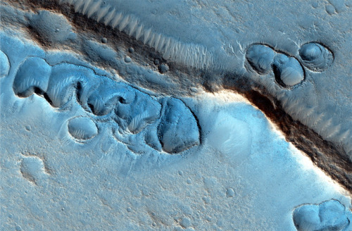 Weird Geological Features Spied on Mars The High-Resolution Imaging Science Experiment (HiRISE) camera carried by NASA's Mars Reconnaissance Orbiter (MRO) has spotted a strange geological feature that, for now, defies an obvious explanation. Found at the southern edge of Acidalia Planitia, small pits with raised edges appear to hug a long ridge. So far, mission scientists have ruled out impact craters and wind as formation processes, but have pegged the most likely cause to be glacial in nature.