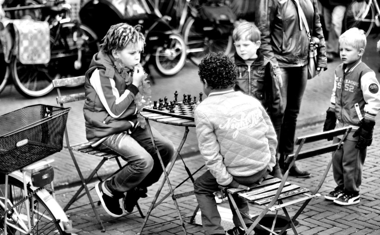 Two boys play chess during Queen's day. 1€ for a game/1€ for a picture.