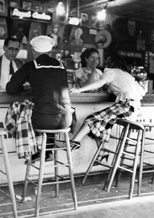 Sailor on shore leave sitting at a soda fountain with young woman. San Diego, 1937 (x)