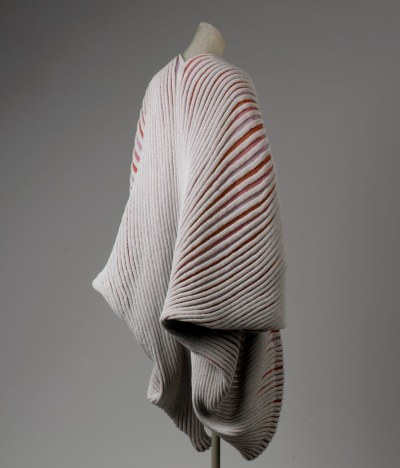 "garcode:  Issey Miyake SS 1985 ""Seashell"" or ""Shell-knit"" coat ""Consistently attentive to cloth's interplay with the human body, by 1985 Issey Miyake was becoming more artificial in his dimensionality, building architectural shapes and infusing the structures of his textiles with permanence and solidity. Miyake manufactured several heat-embossing and texturing processes through the Miyake Design Studio collective (established in 1970) and, alongside designer Makiko Minagawa, manipulated knitwear and synthetics after a garment was constructed by infusing pleats and bumps into otherwise tranquil weaves. The ""Seashell"" coat, also sometimes referred to as the ""Shell-knit,"" is one of his most celebrated and independently iconic creations, with a heat-pleating post-process that coincides with the bands of color in the initial knit design. The organic architecture of the ""Seashell"" coat, as well as the visual splendor of alternate red, lavender, and pink stripes running between elegant gray ribbing, seems inspired by the designer's 1969 apprenticeship with cloth sculptor and design genius Geoffrey Beene."""