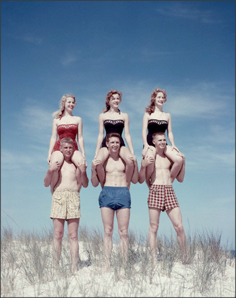 Teens, 1950s Teen girls get shoulder rides from teen boys on beach bluffs, 1954