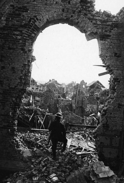 A British soldier looks out upon the ruins of Albert, France. The Western Front, 1918. Tom Aitken