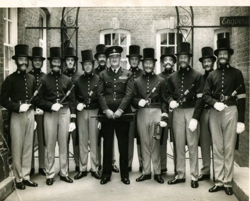 Metropolitan Police officers of the 1960's pose in replicas of the first police uniforms. Their CO, in the centre of the shot is wearing a modern uniform. The officer immediately to the right of centre is carrying a rattle in his left hand. This was the standard way of attracting attention for an officer on patrol prior to the introduction of the police whistle. The wearing of tailcoats and top hats was a deliberate move to distinguish the police as a civil rather than military force. The tailcoat morphed over time into a knee length tunic which gradually shortened into the more practical thigh length one of the late nineteenth century.