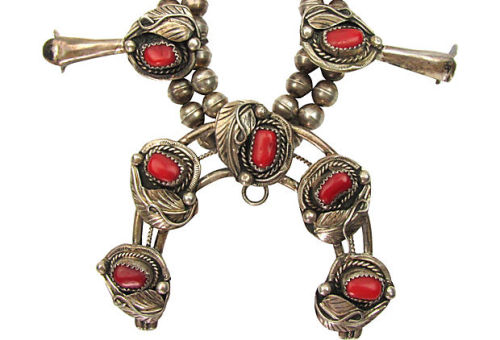 "Squash blossom necklace made by a Navajo silversmith with deep red Italian coral and sterling silver. The central aaja (3""L x .4""W x 2.25""H), or crescent shaped pendant, is a symbol of fertility and abundance, along the blossoms that run up each side of the necklace, decorated with silver leaves, twisted rope and dots. Strung on a double strand of bench-made silver beads with traditional hook and eye clasp. Unsigned. by Ruby + George on One Kings Lane Vintage and Market Finds"
