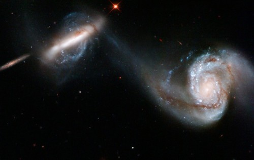 brightestofcentaurus:  Arp 87 Arp 87 is a pair of interacting galaxies located about 300 million light years away in the constellation Leo, the Lion. The two galaxies are spiral galaxy NGC 3808 seen face on in the the right side of the image and companion spiral galaxy NGC 3808A seen edge on at the left. NGC 3808A has an odd rotating ring of stars and material perpendicular to the galactic plane, called a polar ring. The two galaxies appear joined by a swath of material 75,000 light years long. This is strong evidence that the two galaxies passed close to each other, undergoing strong mutual gravity. Further evidence is found in the high number of young, blue stars in the face on galaxy on the right that were formed in a burst of star formation. Eventually, multiple passes should eventually culminate in the two galaxies merging into one system. Image from NASA, information from NASA and HubbleSite.