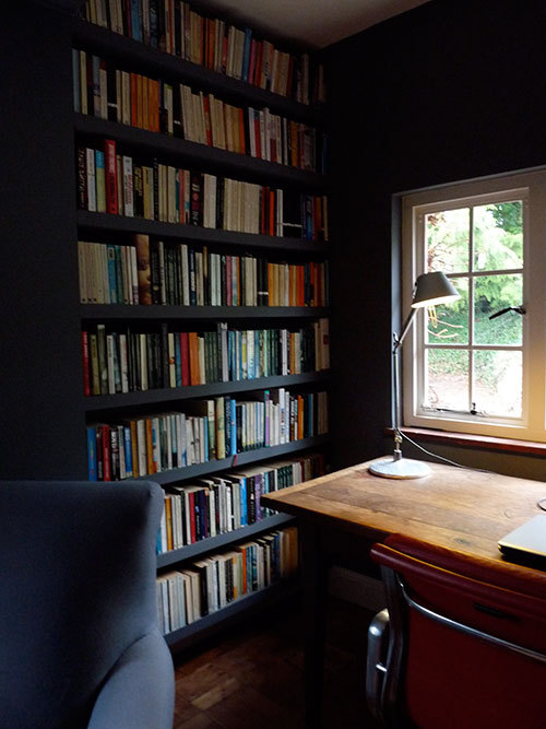 Wonderful study and desk in England.  I'm never quite sure what to call this room. It's part study/part library/large part FIFA games room for the kids. The whole thing (walls and shelves) are painted in Marston's Granite. I wanted it to be dark and cozy. The desk light is a Tolomeo.