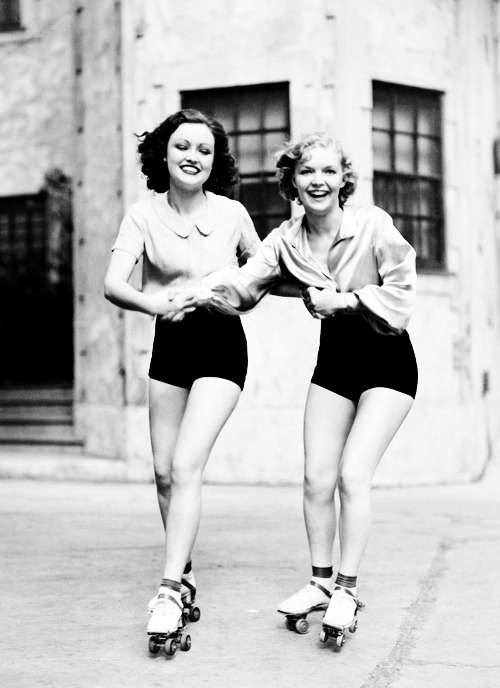 maudelynn:  Portrait of two young women with roller blades skating on the road and smiling