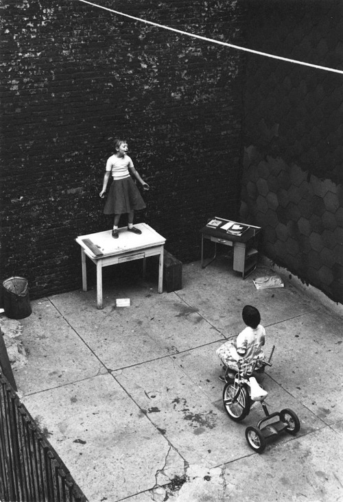 William Gedney Girl standing on desk in courtyard, performing for a seated girl, 1955