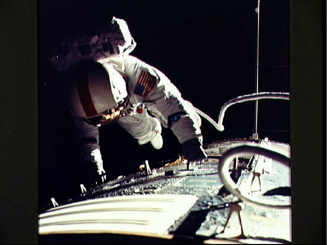 Title: Astronaut Ronald Evans photographed during transearth coast EVA  Description: Astronaut Ronald E. Evans is photographed performing extravehicular activity (EVA) during the Apollo 17 spacecraft's transearth coast. During his EVA Command Module pilot Evans retrieved film cassettes from the Lunar Sounder, Mapping Camera, and Panoramic Camera. The total time for the transearth EVA was one hour seven minutes 19 seconds, starting at ground elapsed time of 257:25 (2:28 p.m.) and ending at ground elapsed time of 258:42 (3:35 p.m.) on Sunday, December 17, 1972.