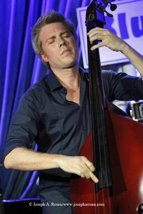 "(via Kyle Eastwood, Larry Coryell and Sons - A Magical Guitar Night at The Blue Note | GuitarInternational.com) ""…Eastwood's band at The Blue Note was tight, top-notch and obviously loving playing together. Eastwood's playing is strong and supple, featuring a wide vibrato that almost makes him sound like he's playing a fretless instrument at times—shades of David Sylvian and Japan… Debra Devi: Can you tell me about the Gibson bass you designed? Kyle Eastwood: It's not really a Gibson per se, it was designed by Bunny Brunel and myself and a guy at the Gibson Custom shop made five or six prototypes, two of which I kept and customized some more myself. It's still the bass I use – I shaped the neck so it's skinnier under the higher strings and it's just balanced ergonomically the way I like. I try a lot of other basses but never seem to find one I like quite as well… Debra: How did you get into African influences? Kyle Eastwood: I've been exposed to a lot of African music living in France and I did some research into South African music when I was writing music for the film Invictus. And living in France I've had the chance to travel a lot through North Africa. There are also a lot of Senegalese musicians in France – I haven't been to Senegal but I've gotten to hear a lot of Senegalese music… Debra: Any jazz influences that come to mind for this album? Kyle Eastwood: I'm drawn to Charles Mingus and other jazz payers from the fifties and sixties. He's a great role model for me as a bassist who was also a bandleader and composer. Art Blakely's groups, too, from the late fifties, early sixties I've always liked that sound, and writing for a group with two horns, like mine. Without having to actually travel around with a big band! [laughs] I grew up listening to sixties and seventies funk and really digging it. That's the stuff that made me want to pick up the bass. I started teaching myself those songs…"""