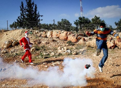 Happy Christmas from Palestine !Santa Claus look at the Palestinian young guy getting teargas was shot by Israeli soldiers at nonviolent demonstration against the apartheid wall in bil'in village!
