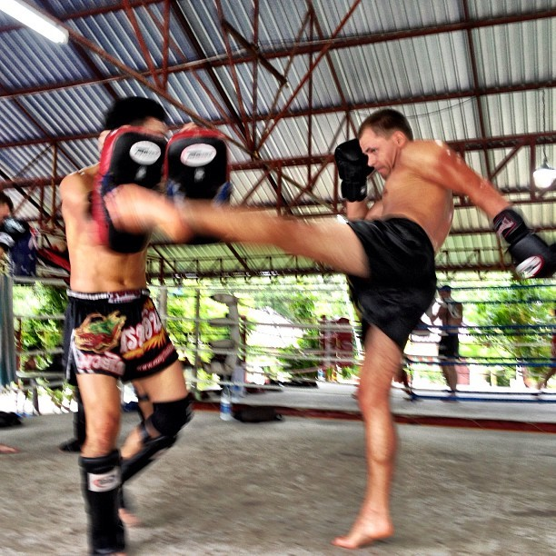 Kai working with a student to correct his technique and get his Muay Thai on track to perfection