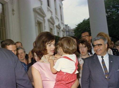 First Lady Jacqueline Kennedy holds John F. Kennedy, Jr. (playing with his mother's necklace) in the North Portico of the White House, Washington, D.C., following Major L. Gordon Cooper's National Aeronautics and Space Administration (NASA) Distinguished Service Medal (DSM) presentation ceremony.
