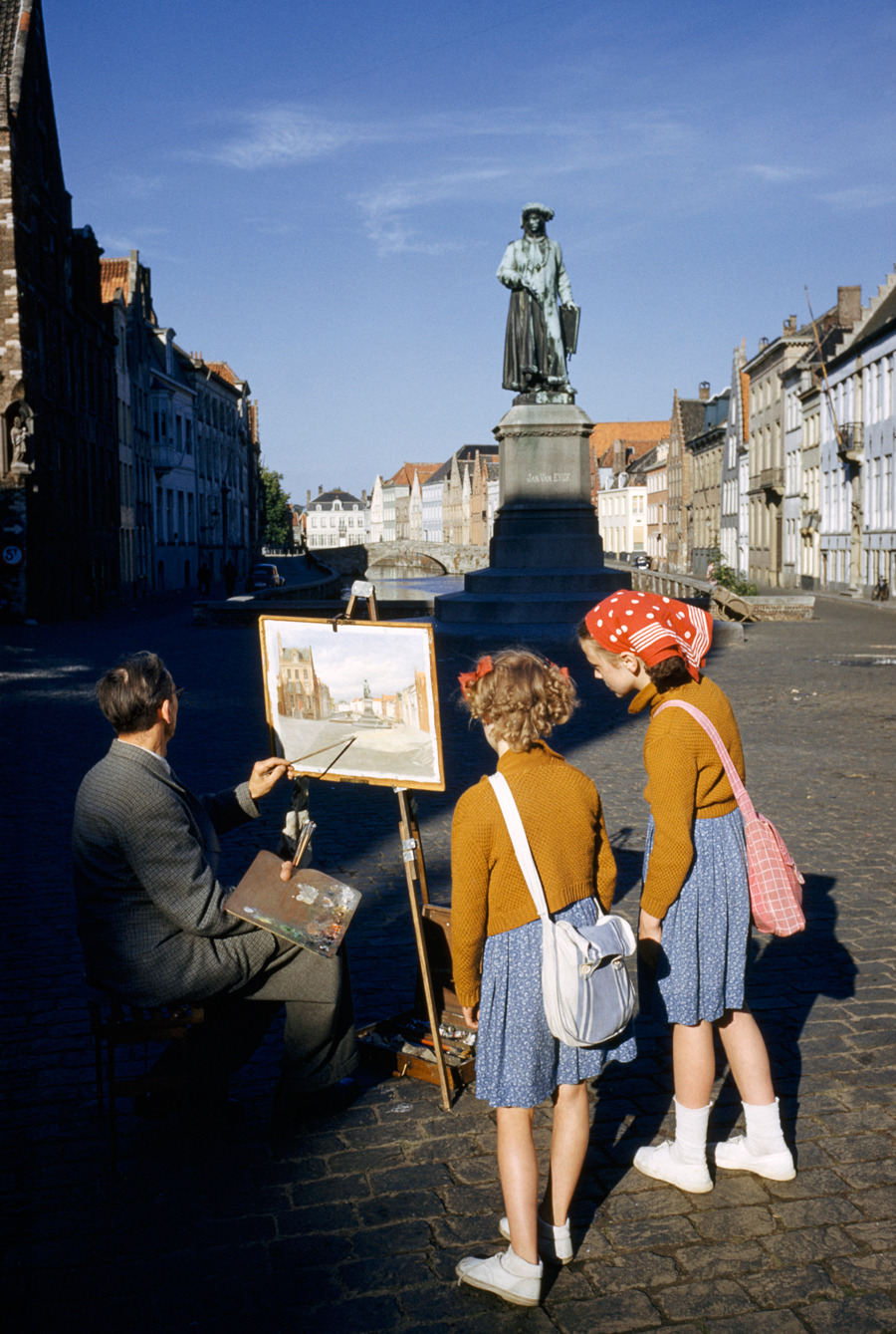 sews:      natgeofound:  Girls watch artist painting picture of statue of Flemish artist in Bruges, Belgium, May 1955.Photograph by Luis Marden, National Geographic