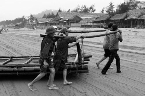 Carrying a bamboo raft onto the beach