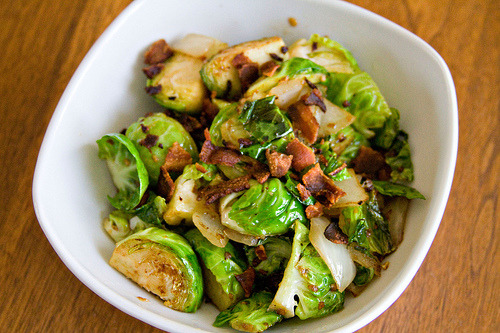Brussels Sprouts with Garlic, Onion, and Bacon 1/2 sweet onion, chopped 2 slices bacon 2 cloves garlic, minced 6 brussels sprouts In a skillet over medium heat, add the bacon and fry until browned. Remove to a paper towel to drain, and then add the onions and garlic to the pan and sauté until the onions are tender. Quarter the brussels sprouts and add to the pan. Sauté until browned. Season with salt and pepper if desired. Cook 2-3 more minutes and then transfer to a bowl to serve. Crumble the cooked bacon into pieces and sprinkle over the top. Serves 2 as a side.