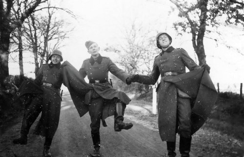 bag-of-dirt:  A brief moment of merriment. Three German soldiers, covered in hay, lighten their mood by amusing themselves on a country lane during the often tedious days and weeks without seeing combat; something familiar to all soldiers during wartime. Russia. 1941.