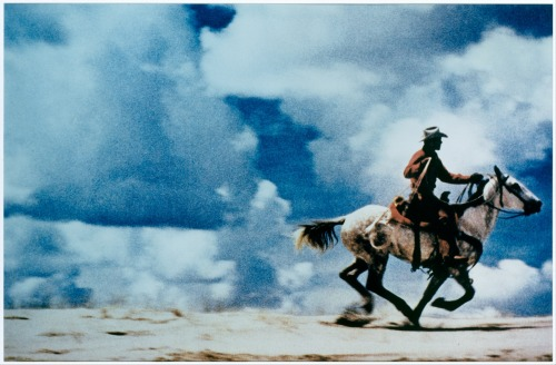 "cavetocanvas:  Richard Prince, Untitled (cowboy), 1989 From the Metropolitan Museum of Art:  In the mid-1970s Prince was an aspiring painter who earned a living by clipping articles from magazines for staff writers at Time-Life Inc. What remained at the end of the day were the advertisements, featuring gleaming luxury goods and impossibly perfect models; both fascinated and repulsed by these ubiquitous images, the artist began rephotographing them, using a repertoire of strategies (such as blurring, cropping, and enlarging) to intensify their original artifice. In so doing, Prince undermined the seeming naturalness and inevitability of the images, revealing them as hallucinatory fictions of society's desires. ""Untitled (Cowboy)"" is a high point of the artist's ongoing deconstruction of an American archetype as old as the first trailblazers and as timely as then-outgoing president Ronald Reagan. Prince's picture is a copy (the photograph) of a copy (the advertisement) of a myth (the cowboy). Perpetually disappearing into the sunset, this lone ranger is also a convincing stand-in for the artist himself, endlessly chasing the meaning behind surfaces. Created in the fade-out of a decade devoted to materialism and illusion, ""Untitled (Cowboy)"" is, in the largest sense, a meditation on an entire culture's continuing attraction to spectacle over lived experience."