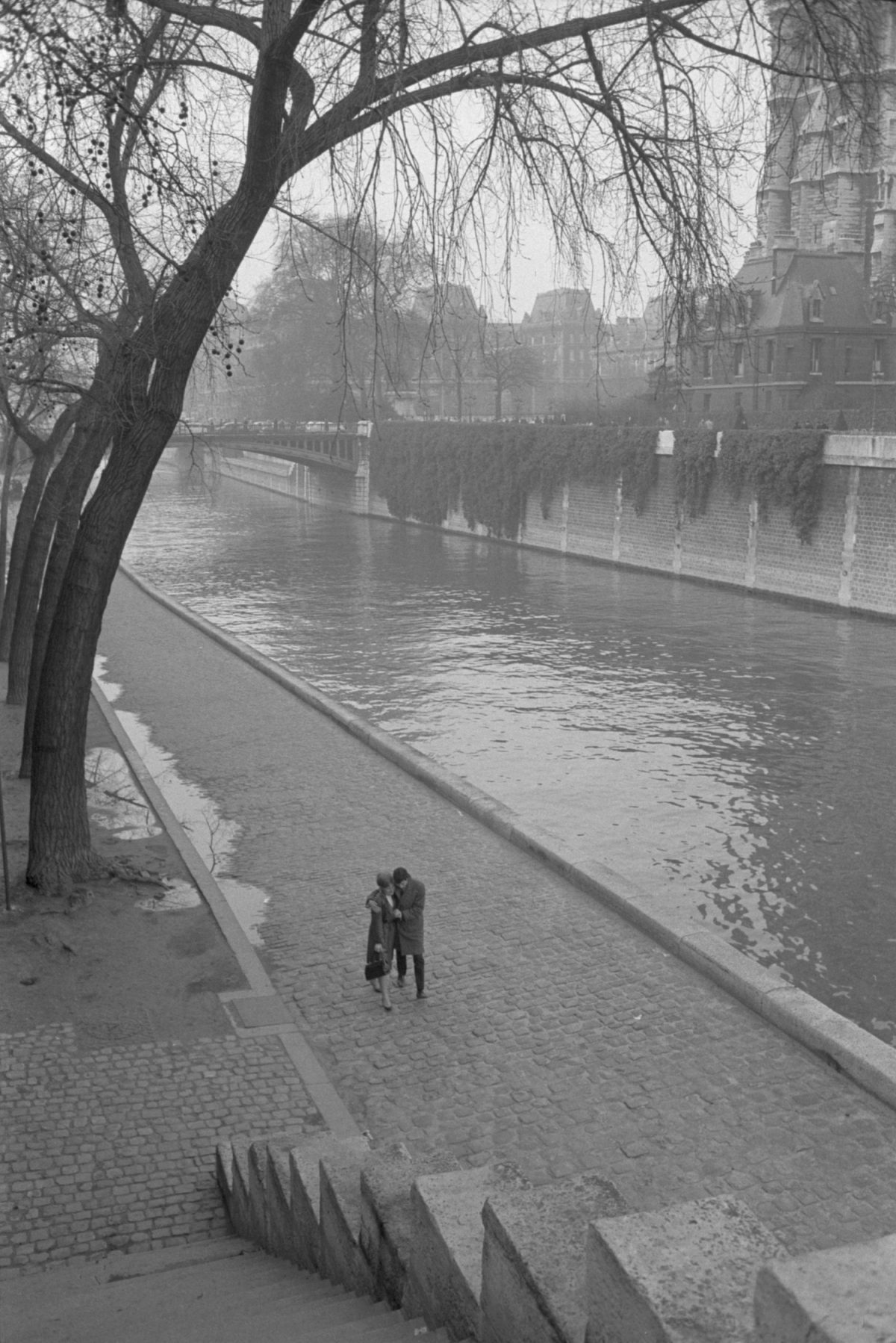 Toni Frissell.A couple walking along the Seine River. 1950s #toni frissell #black and white #vintage#photography#street photography#art#history #black and white photography #vintage photography#1950s