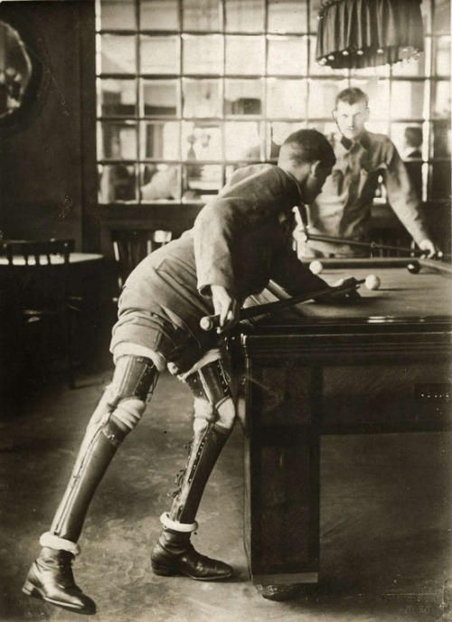 gdfalksen:  A soldier who lost both his legs in the first World War, playing a game of billiards, 1915.