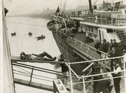 Seriously wounded German prisoner of war is brought aboard an English warship on a stretcher in Oostende. Belgium, 1914. From: The Dutch National Archives