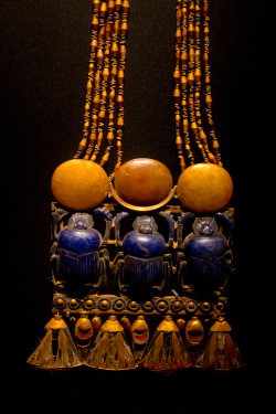 ancientart:  A pectoral with three scarab beetles clasped to a necklace (partly shown) which was discovered from the intact KV62 tomb of Tutankhamun. This jewellry depicts Scrab Beetles or Khepri, pushing the sun. It is one of the treasures found from Tutankhamun's tomb who ruled during the 18th dynasty of Egypt's New Kingdom. Photo taken by Dmitry Denisenkov at the Tutankhamun: The Golden King and Great Pharaohs exhibit. Courtesy the Egyptian Museum, Cairo.
