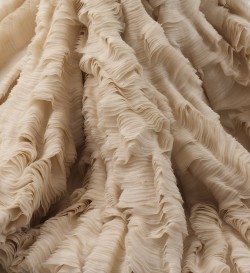"fashioninhistory:  Oyster Dress (Detail) Alexander McQueen   Spring/Summer 2003 A number of gowns in Alexander McQueen's ""Transitions"" collection of spring/summer 2003 appear to be poetic renderings of a disaster at sea. While a similar dress appeared colored like the plumage of a tropical bird, this gown of sand-colored organza recalls the mille-feuille ridging on the surface of a shell. The hem of the skirt, like the wavy lip of a giant mollusk, further emphasizes the seashell quality of the gown. But unlike Aphrodite, who was born in the foam of the sea and borne to shore on a scallop, McQueen's beauty is a bruised pearl encased in a deconstructing oyster, the tumbled survivor of the violent action of waves."