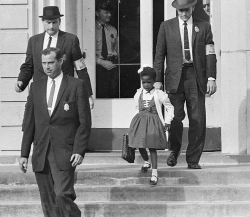 "fashionwolf:  blackhistoryday:  ""Don't be afraid."" That's what Ruby Bridges's mother told her on November 4, 1960. Little Ruby listened carefully to the advice. Soon, four United States federal court marshals, or officers, arrived at the Bridges family home in New Orleans, La., to drive the first grader to William Frantz Public School. A screaming mob was waiting. People stood near the building shouting. Ruby held her head high. With the marshals surrounding her, the 6-year-old walked into the school and into history  i heard this sad story about these students who were the first black students in an american school and no one talked to them and anyway on the final day when they graduated and got there certificates when one fo the guys went up no one clapped, they only clapped for the white people. so mean :("