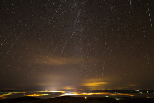 "Behold: The Geminids! ""This is a composite of all the Geminid meteors captured over Pendleton, Oregon on the evening of December 13, 2012. I took these from Emigrant Hill. In the valley below, you can see the light ""footprint"" of Pendleton, Mission, the Wildhorse Casino, and several other smaller towns. Fog has enveloped most of the cities below.""      — Thomas W. Earle"