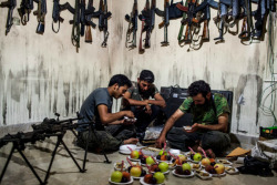 simply-war:  Free Syrian Army soldiers prepare fruit plates for their fellow fighters in their base's weapons storage room. 2012. Bryan Denton.